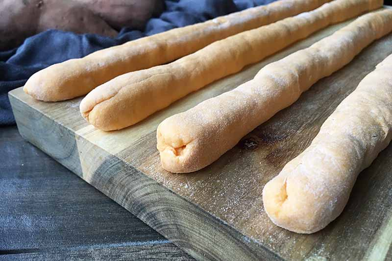 Horizontal image of four shaped light orange logs of dough on a wooden cutting board.