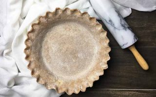 Horizontal image of a crimped pie shell next to a rolling pin and a white towel.