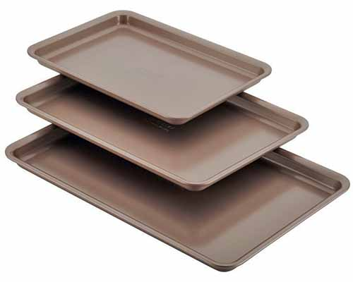 Anolon 3-piece set of rimmed pans in graduated sizes in bronze, isolated on a white background.