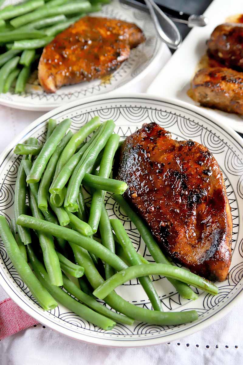 Vertical image of two white dinner plates with a black patter, with portions of balsamic chicken breast and steamed green beans, with a white ceramic serving platter of more of the poultry entree, on a red and white striped cloth, with silverware.