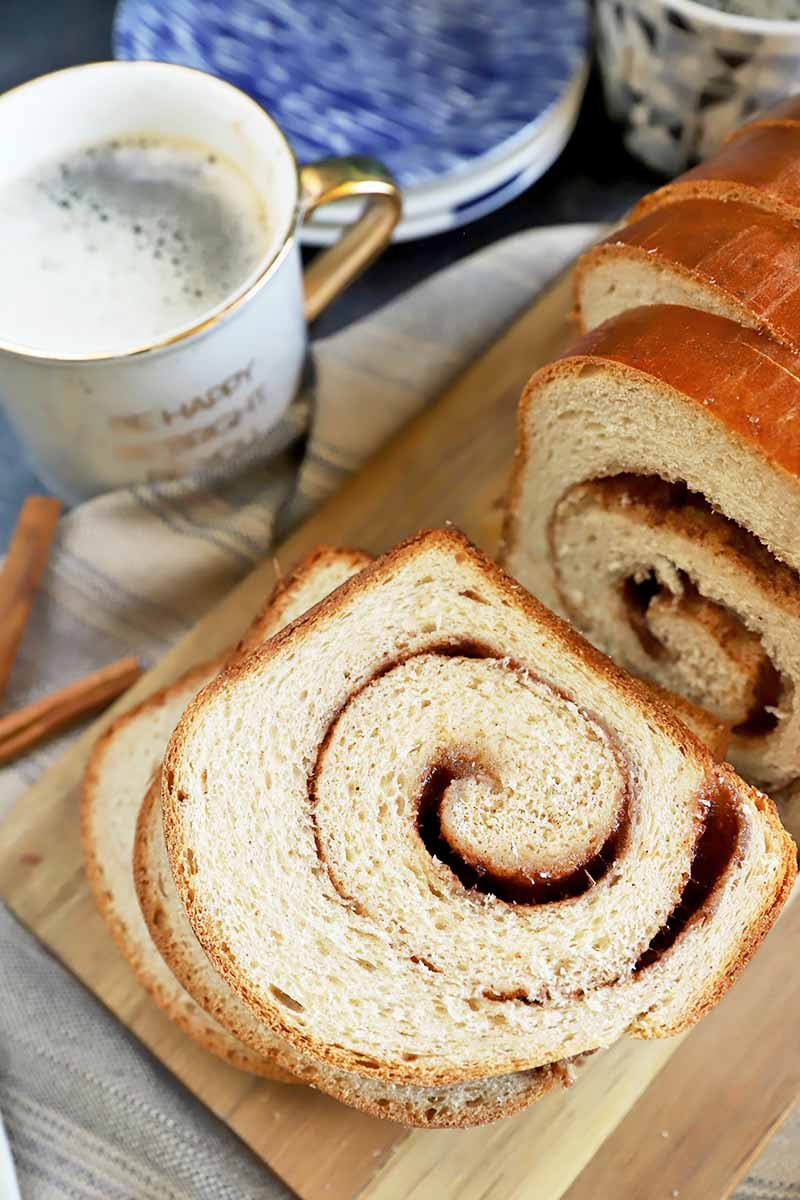 Vertical image of fluffy bread slices with a swirl filling stacked on top of each other next to plates and mugs of coffee.