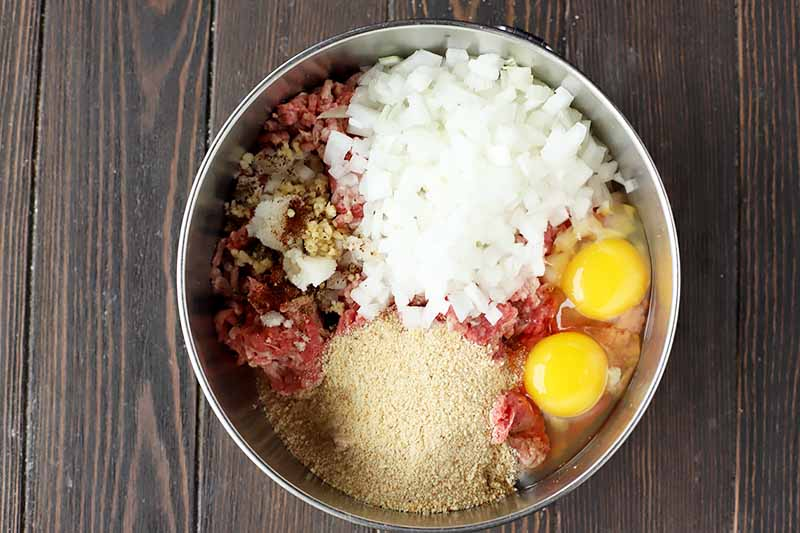 Horizontal image of eggs, onions, breadcrumbs, and other seasonings on top of raw ground beef in a metal bowl.