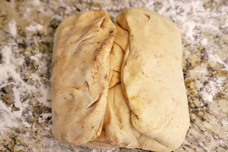 Horizontal image of a folded large piece of spiced dough.