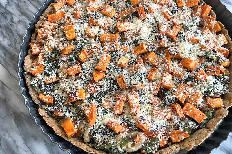 Overhead closely cropped horizontal image of a blind baked tart crust in a metal pan, filled with a misture of roasted sweet potatoes and sauteed Swiss chard, and topped with grated pecorino cheese.