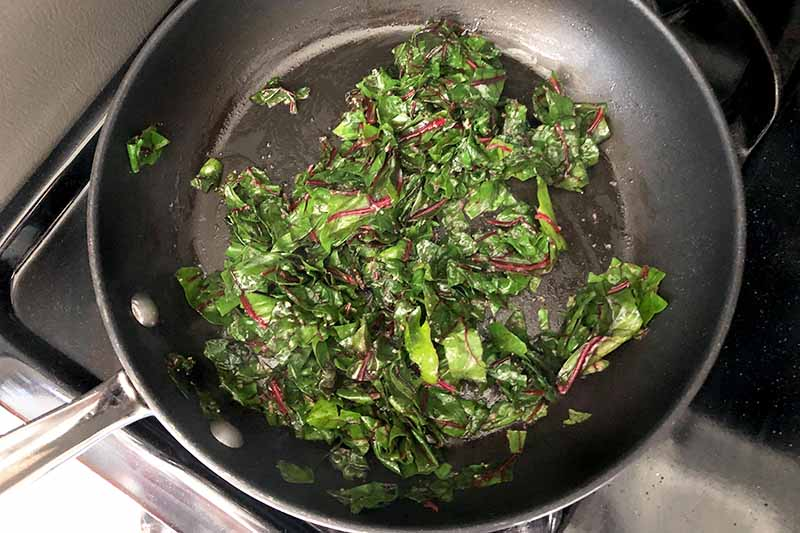 Horizontal overhead closely cropped image of a nonstick frying pan of sauteed green Swiss chard on a stove.
