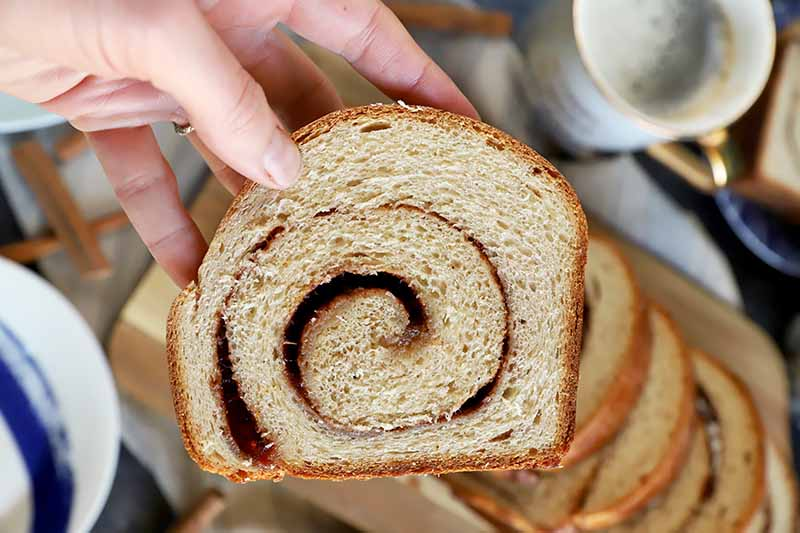Horizontal image of a hand holding a slice of bread with a swirled filling.