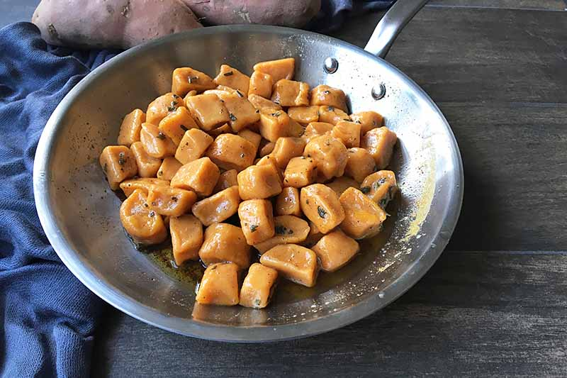 Horizontal image of a skillet with browned butter and orange gnocchi.