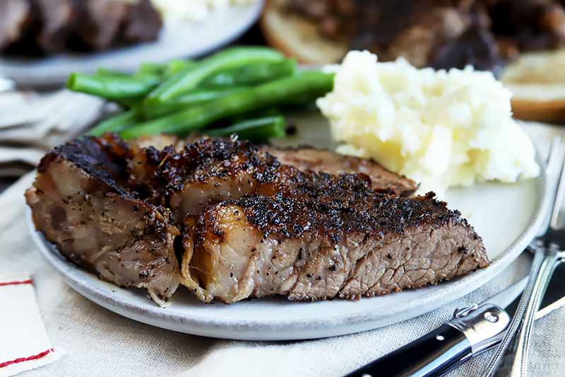Horizontal image of sliced and seasoned meat with green beans and mashed potatoes next to silverware.