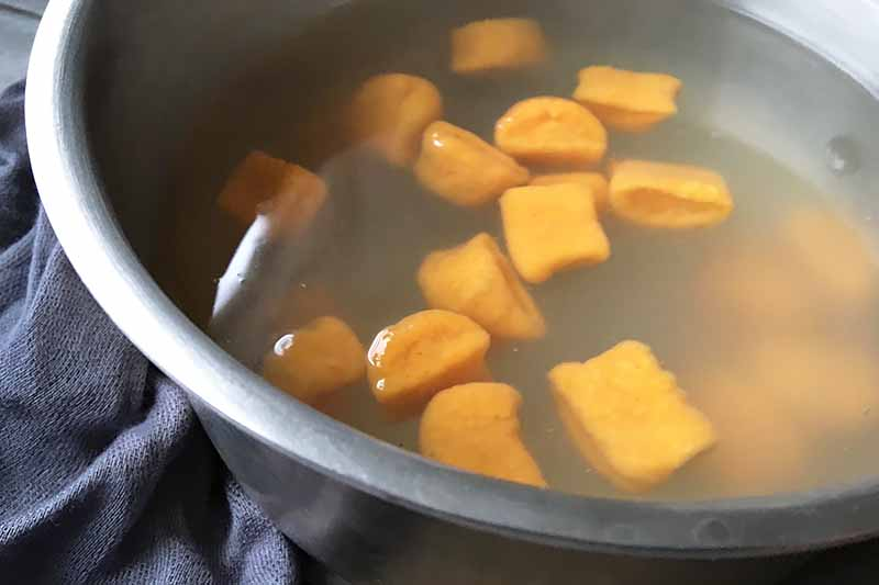 Horizontal image of a pot filled with cloudy water and orange dumplings floating.