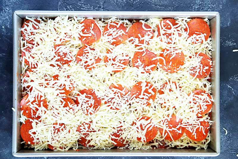 Horizontal overhead image of a rectangular metal baking pan of noodles topped with sauce, shredded cheese, and sliced pepperoni, on a gray surface.