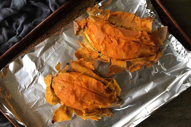Horizontal image of two skinned sweet potatoes on a baking sheet lined with foil.