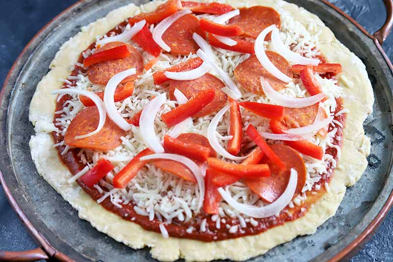 Horizontal image of a homemade pizza topped with red sauce, shredded cheese, sliced onions and red bell pepper, and pepperoni, on a metal pan, ready to go in the oven.