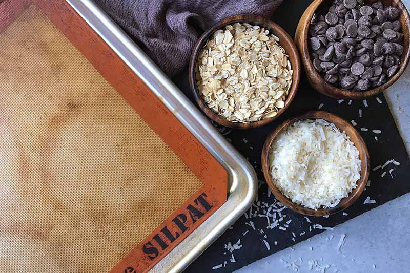 Horizontal image of a baking sheet with a silicone mat next to bowls of oats, coconut, and candies.