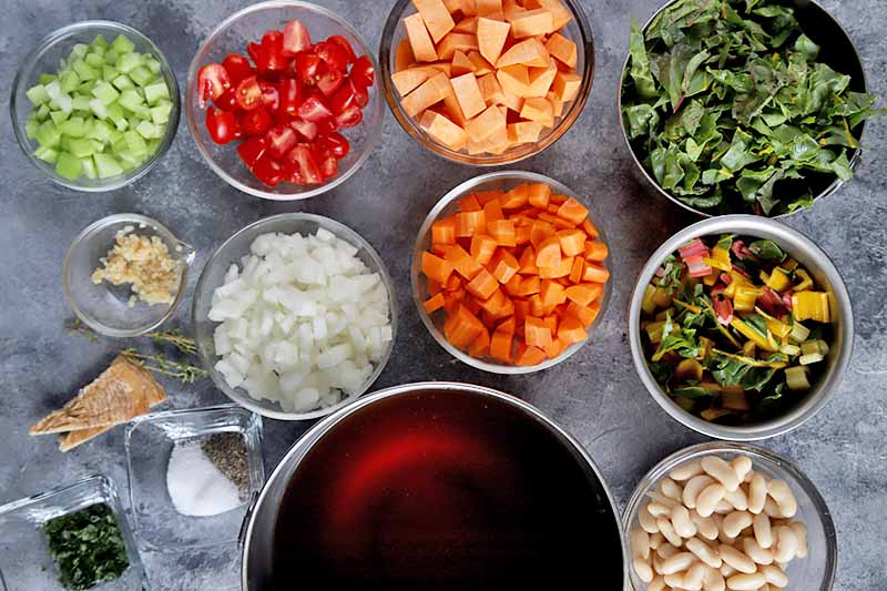 Horizontal image of assorted prepared vegetables, beans, broth, and seasonings.