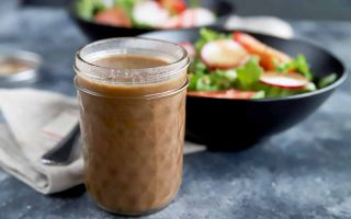 Horizontal image of a glass jar with a brown creamy liquid in front of a napkin, fork, and bowls of salad.