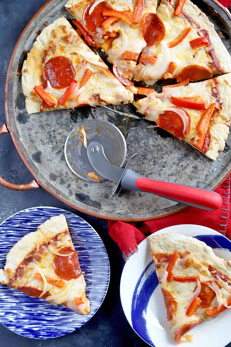 Vertical overhead image of four triangular pieces of pepperoni, bell pepper, and onion pizza on a metal pan, with slices on two blue and white plates at the bottom of the frame, and a metal cutting wheel with a red handle, on a gray surface with a red cloth.