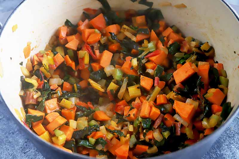Horizontal image of assorted softened cut vegetables in a pot.