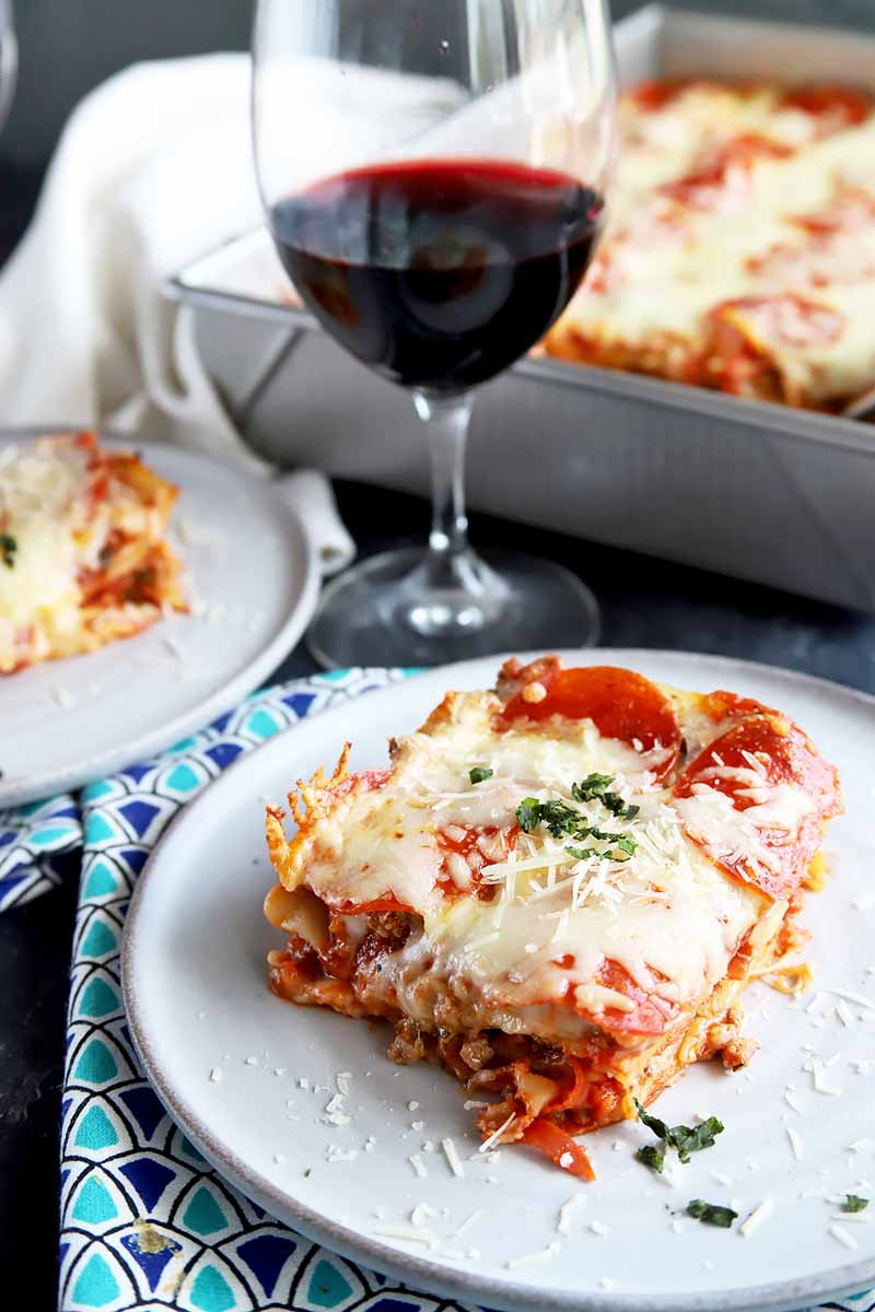 Vertical image of two portions of lasagna on plates, with the remainder of the dish in a large metal baking pan in the background, with a folded white cloth towel, dark and light blue patterned cloth napkin, and a glass of red wine.