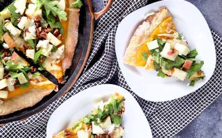 Horizontal overhead closely cropped image of two plated slices and a serving dish of homemade pizza with apples, arugula, cheese, pecans, and squash puree, on a black and white checkered cloth on a mottled blue-gray surface.