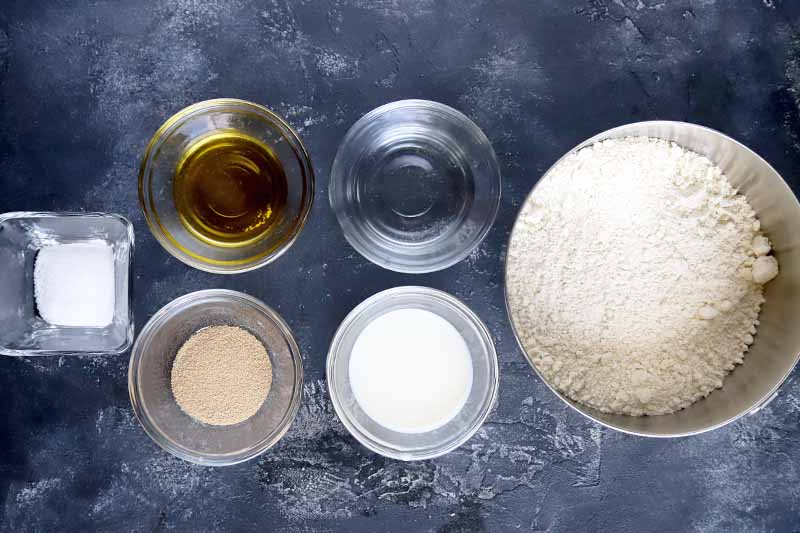 Horizontal overhead image of three small round glass bowls, one small square glass bow, and a medium-sized stainless steel bowl of salt, oil, yeast, water, kefir, and einkorn flour, on a mottled gray surface.