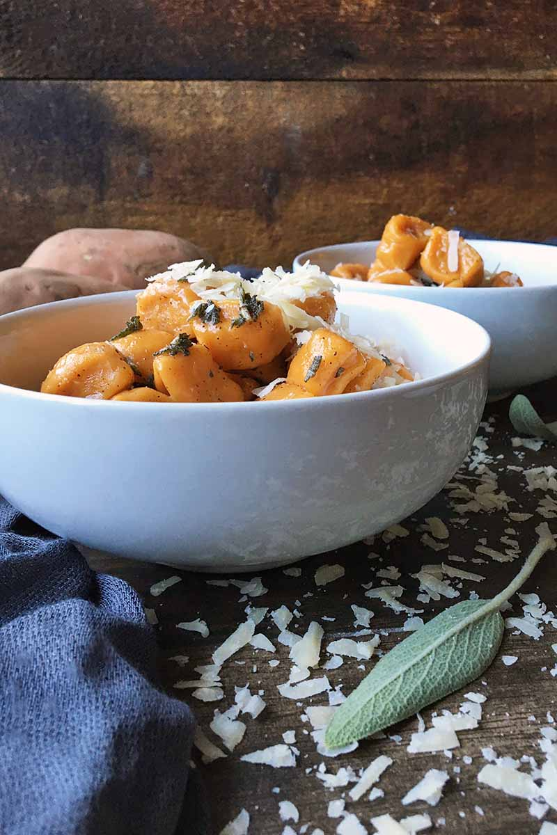 Vertical image of two white bowls with orange gnocchi and cheese on a table with sage leaves and shredded cheese.
