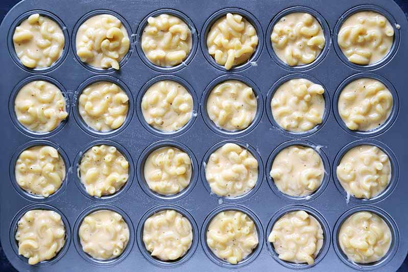 Overhead horizontal image of portion of elbow macaroni with cheese sauce evenly distributed in a metal mini muffin tin.