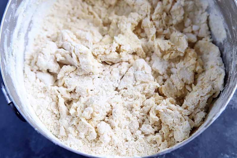 Overhead closely cropped horizontal image of a stainless steel bowl filled with a lumpy flour mixture.