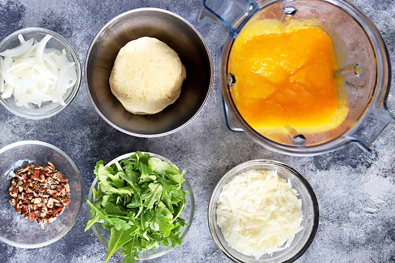 Horizontal closely cropped overhead image of glass and metal bowls of various sizes, filled with sliced onion, chopped pecans, pizza dough, arugula, crumbled cheese, and squash puree, on a white and gray sponge-painted surface.