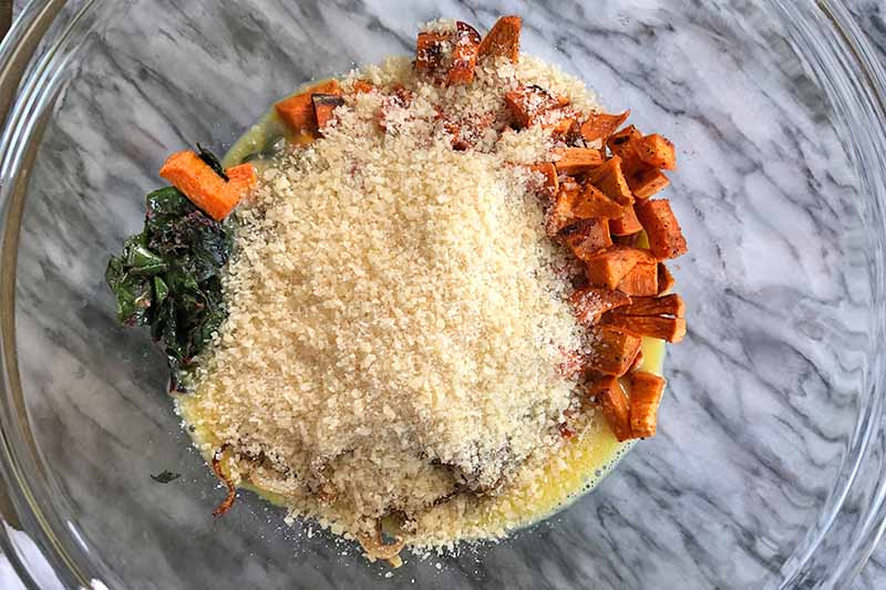 Horizontal overhead image of roasted cubed sweet potato, sauteed Swiss chard, raw egg, and grated pecorino cheese in a large glass mixing bowl, on a gray marble surface.