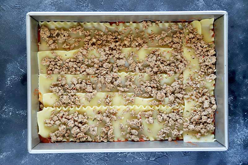 Horizontal overhead image of a large rectangular metal baking pan of lasagna noodles topped with cooked grown turkey, on a mottled blue-gray surface.