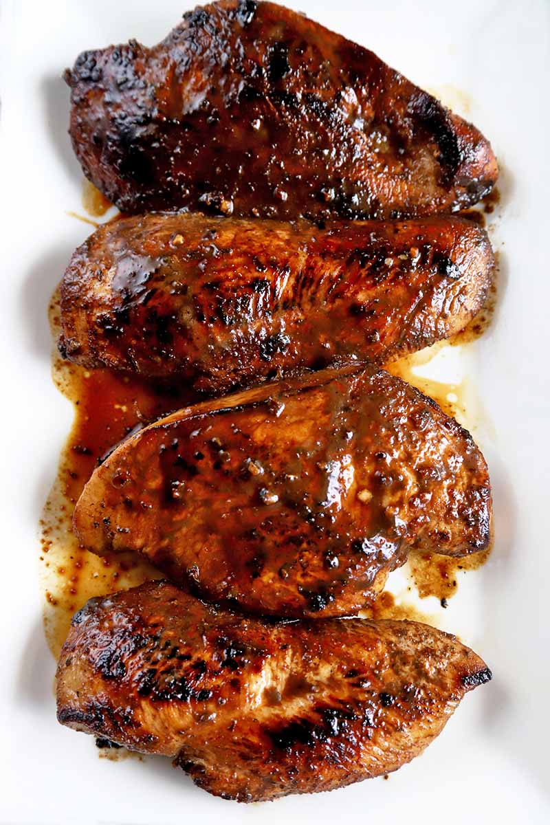 Overhead vertical image of four balsamic glazed pieces of poultry on a white ceramic serving platter.