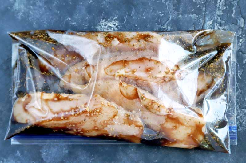 Horizontal overhead image of chicken breasts marinating in a mixture of balsamic vinegar and other ingredients in a clear plastic zip-top bag, on a dark blue-gray surface with white sponge painted splotches.