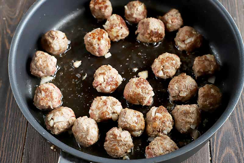 Horizontal image of a pan with browning meatballs.