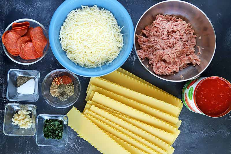 Horizontal overhead image of square and round glass and metal bowls of various sizes, filled with sliced pepperoni, spices, garlic, chopped parsley, ground turkey, shredded cheese, and tomato sauce, with a pile of uncooked lasagna noodles, on a blue-gray surface.