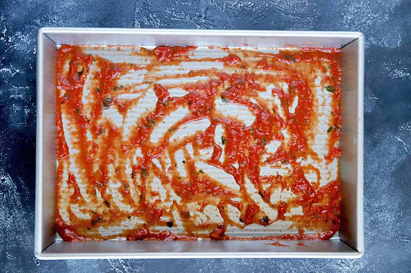 Horizontal overhead image of a thin layer of tomato sauce spread in the bottom of a large rectangular metal baking pan, on a sponge-painted blue-gray and white surface.