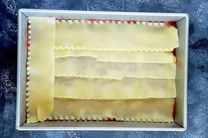 Horizontal overhead image of cooked lasagna noodles arranged in a single layer over a thin coating of red tomato sauce in the bottom of a large rectangular metal baking pan, on a blue-gray surface.