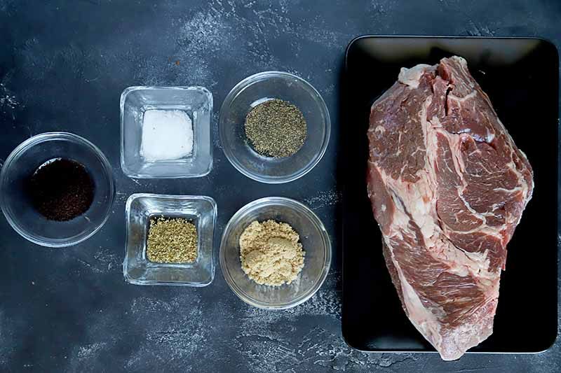 Horizontal image of seasonings in glass dishes next to a large piece of raw meat.