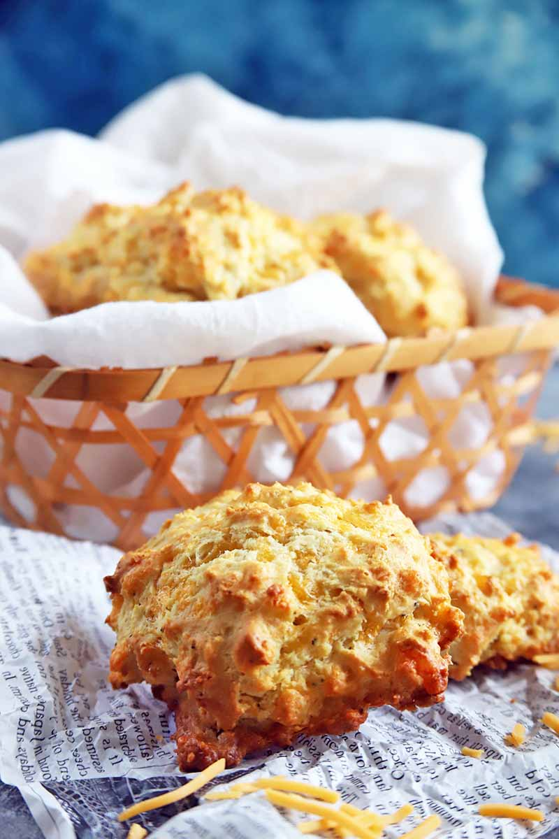 Vertical image of cheddar garlic biscuits in a basket lined with tissue and on tissue paper printed to look like newspaper in the foreground, with scattered shredded cheese, against a mottled blue backdrop.