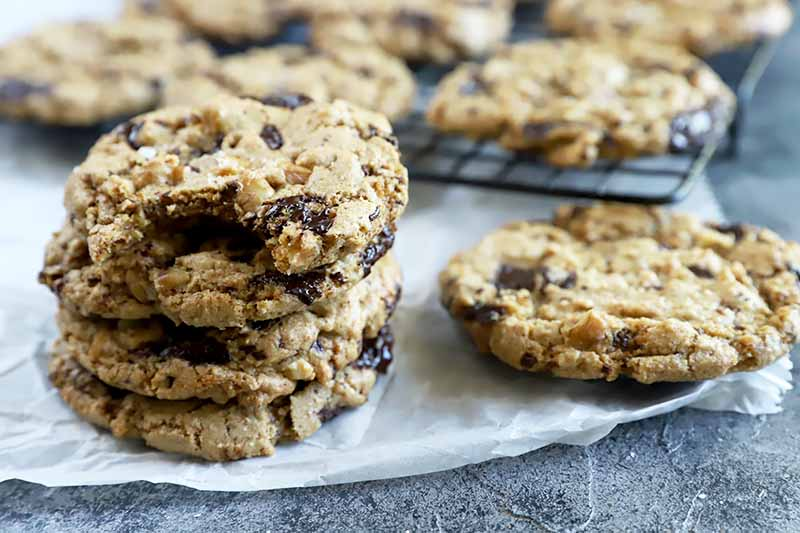 Horizontal image of a chocolate chip walnut cookies, some stacked, and some on a cooling rack.