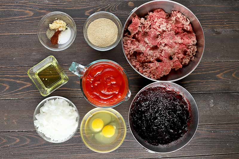Horizontal image of ground beef, eggs, jam, ketchup, and other ingredients in various bowls on a wooden surface.
