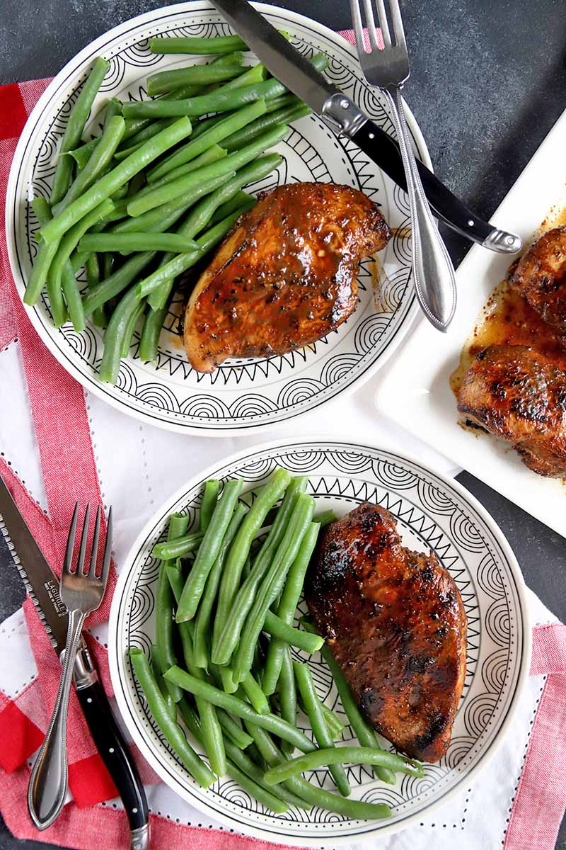 Vertical overhead image of two white patterned plates of marinated chicken and steamed green beans, with silverware, on white cloth napkins with red borders, next to a white ceramic platter of the poultry entree, on a gray surface.
