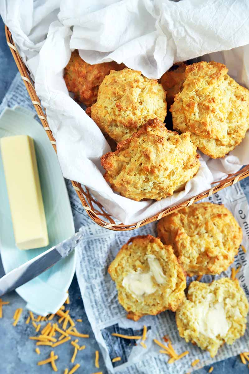 Vertical over head image of drop biscuits in a basket lined with parchment paper and on tissue paper printed to look like newsprint, next to a stick of butter on a ceramic dish with a knife, on a gray surface with scattered shredded cheese.