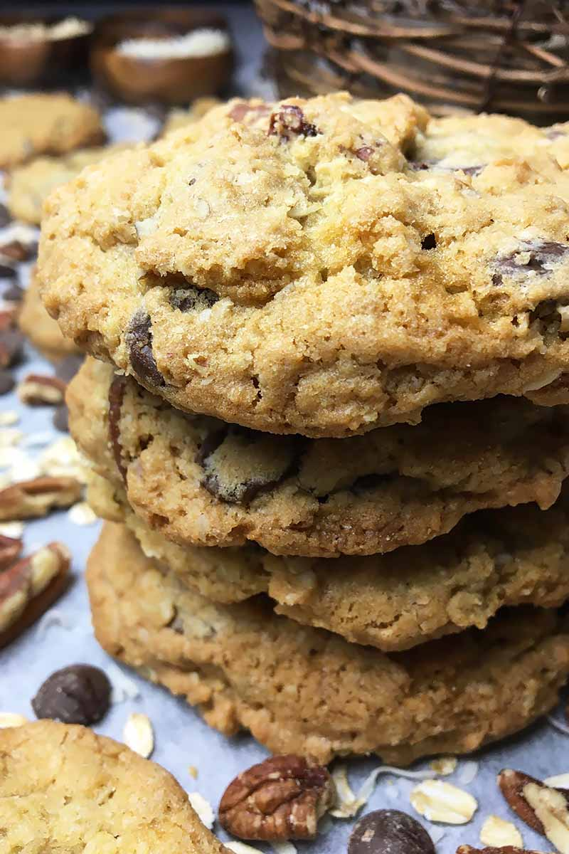Vertical close-up image of a stack of cookies with nuts, oats, and shredded coconut.