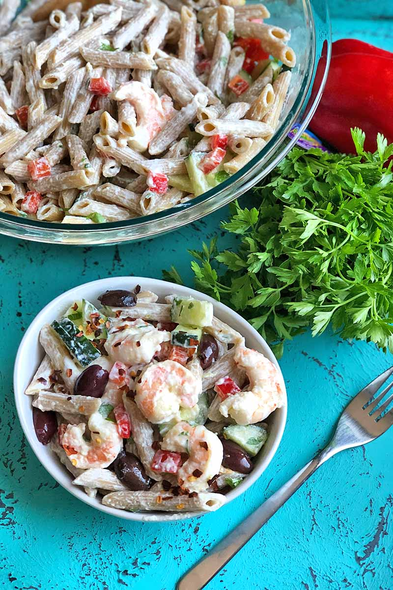 Vertical overhead image of a large glass mixing bowl and a white ceramic bowl of shrimp and pasta salad, with a fork, a bunch of parsley, and a red bell pepper, on a blue painted and weathered surface.