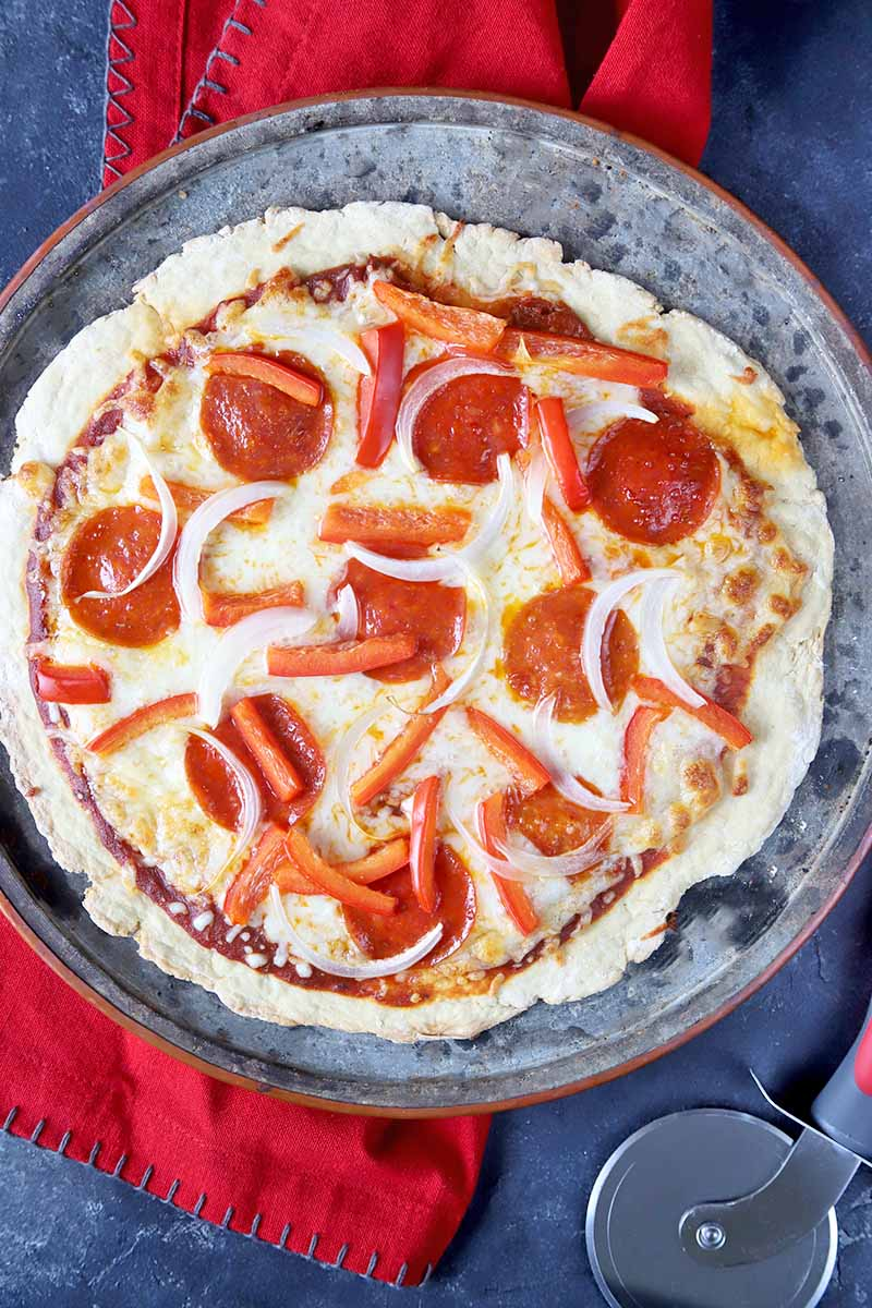 Vertical overhead image of a homemade pepperoni, red bell pepper, and onion pizza on a metal pan, on top of a red cloth on a gray surface, with a cutting wheel tool.
