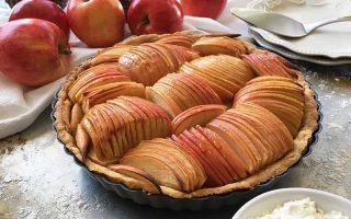 Horizontal image of a French apple tart in front of whole fruit.