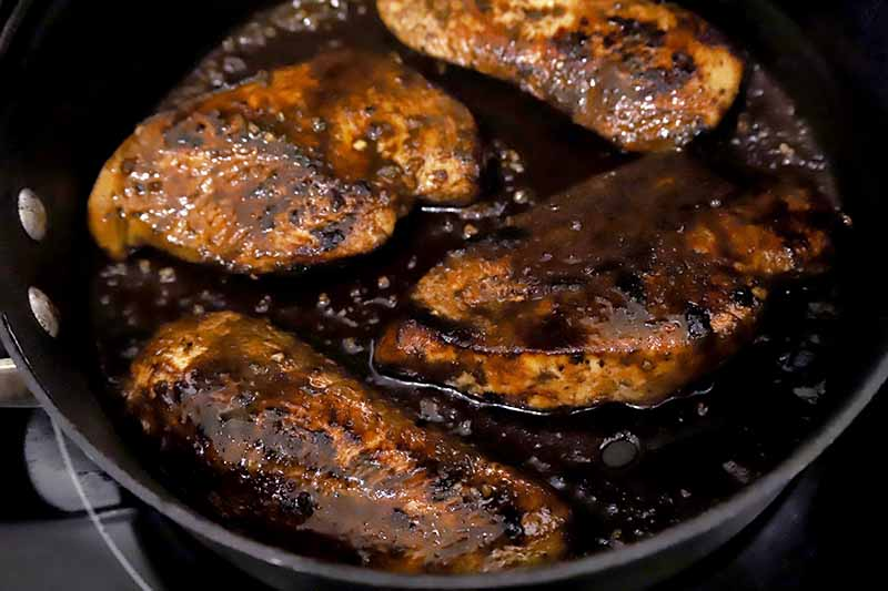 Close-up horizontal image of balsamic glazed chicken in a large skillet.
