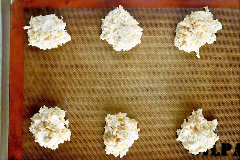 Horizontal overhead image of six portioned dollops of drop biscuit dough on a silicone Silpat pan liner on top of a metal baking sheet.