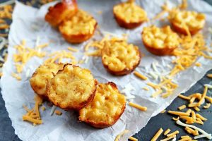 Overhead horizontal image of miniature baked macaroni appetizers on a crumpled piece of white parchment paper, with shredded cheddar cheese scattered on the surface, on a gray table.