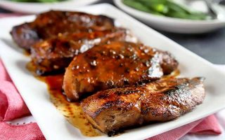 Horizontal image of four balsamic marinated chicken breasts on a white rectangular ceramic serving platter, on top of a white cloth with a red border on a gray table, with two plates of steamed green beans in soft focus in the background.